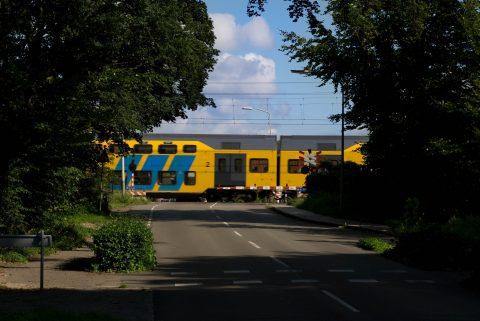 Een NS-trein passeert een spoorwegovergang, foto: Sweco