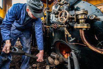 Stoker Wilco Steur schept de eerste scheppen biokool in locomotief 5, foto: Benno Ellerbroek
