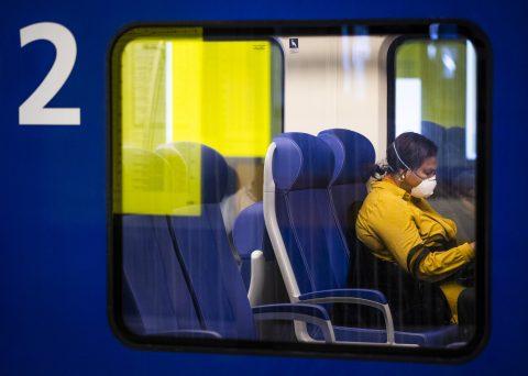 Een reiziger met een mondkapje in een NS-trein, foto: ANP