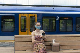 Vrouw draagt een mondkapje op het perron in Amsterdam, foto: ANP