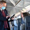 Een conducteur van Deutsche Bahn controleert kaartjes in coronatijd