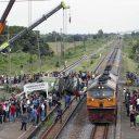 Een trein rijdt voorbij een wrak van een bus die in botsing is gekomen met een andere trein bij het station Khlong Kwaeng Klan railway in de provincie Chachoengsao in Thailand, foto: ANP