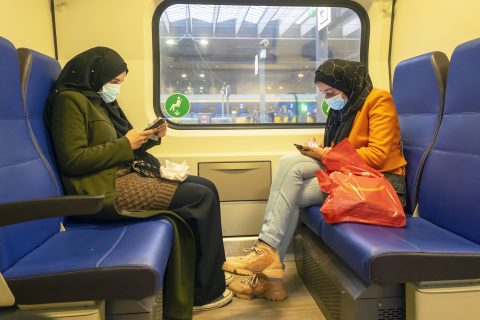Twee jonge moslima's zitten in de trein op hun telefoon te kijken