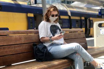 Reiziger met mobiele telefoon tijdens de coronacrisis, foto: NS