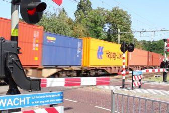 Een goederentrein passeert een spoorwegovergang in Oisterwijk