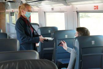 Conducteur met mondkapje controleert reiziger ICE trein