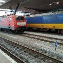 Een goederentrein van DB Cargo en een NS-trein op station Rotterdam centraal