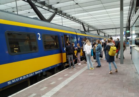 Reizigers met mondkapjes op het perron van Rotterdam Centraal