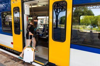 Een reiziger met een mondkapje stapt in een NS-trein, foto: ANP