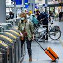 Reizigers met een mondkapje in de spits op station Den Haag Centraal, foto: ANP